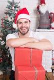 Человек в улыбке шляпы santa с коробками на рождественской елке Стоковые Изображения RF