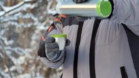 Человек в холоде льет горячий чай от thermos в кружку Рука с кружкой горячего конца-вверх чая сток-видео
