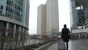 Человек в черной шинели с багажом идет вдоль улицы города с небоскребами видеоматериал