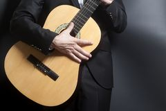 Человек в черном костюме с акустической классической гитарой Стоковое Фото
