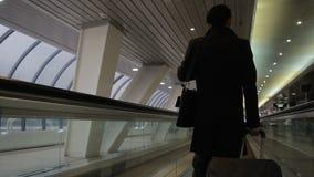 Человек в черном пальто с чемоданом едет назад на эскалаторе авиапорта сток-видео