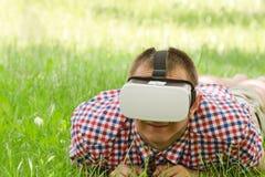 Человек в шлеме виртуальной реальности лежит на зеленой траве Стоковые Фото