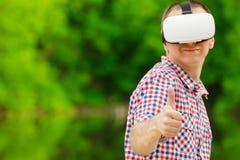 Человек в шлеме виртуальной реальности на фоне природы большие пальцы руки вверх Стоковые Изображения