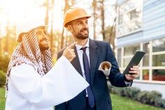 Человек в шлеме показывает план строительства для арабского бизнесмена Стоковые Изображения RF