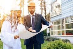 Человек в шлеме показывает план строительства для арабского бизнесмена Стоковые Фото