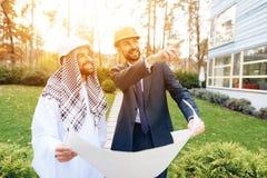 Человек в шлеме показывает план строительства для арабского бизнесмена Стоковые Изображения