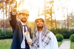 Человек в шлеме показывает план строительства для арабского бизнесмена Стоковое Фото
