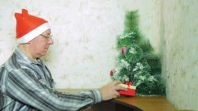 Человек в шляпе Санта Клауса кладет подарки на рождество для семьи под рождественскую елку сток-видео