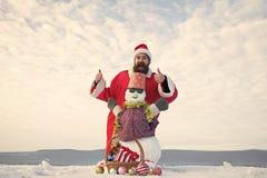 Человек в шляпе santa показывая большие пальцы руки поднимает руки стоковая фотография