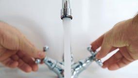 Человек в bathroom с 2 руками регулирует температуру воды от крана видеоматериал