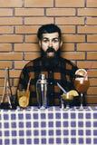 Человек в checkered рубашке на предпосылке кирпичной стены, голубой скатерти Стоковое Изображение
