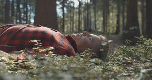 Человек в checkered рубашке отдыхая с закрытыми глазами в лесе сток-видео
