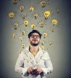 Человек в eyeglasses с smarpthone производящ множество успешных идей Стоковая Фотография RF
