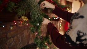 Человек в kniited венке рождества свитера вися над каменным подлинным камином украшенным с красочной проблескивая гирляндой видеоматериал