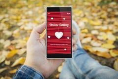 человек в smartphone датировка парка онлайн стоковая фотография