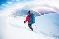 Человек в snowshoes в горах в зиме Стоковые Изображения