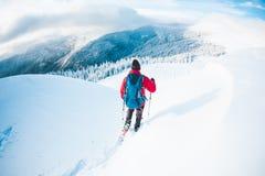 Человек в snowshoes в горах в зиме Стоковая Фотография