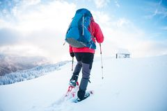 Человек в snowshoes в горах в зиме Стоковые Фото