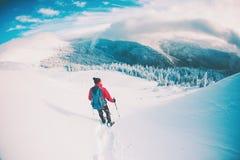 Человек в snowshoes в горах в зиме Стоковое Фото