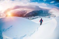 Человек в snowshoes в горах в зиме Стоковое фото RF