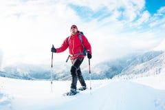Человек в snowshoes в горах в зиме Стоковая Фотография RF