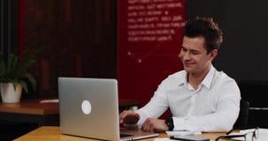 Человек говорит на видео-звонке на его компьтер-книжке в офисе Молодой привлекательный бизнесмен в белом соитии показа рубашки вы видеоматериал