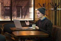 Человек говорит онлайн в кафе через посыльный интернета на компьютере стоковое изображение rf