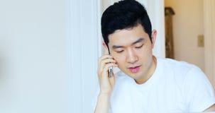 Человек говоря на мобильном телефоне дома 4k акции видеоматериалы