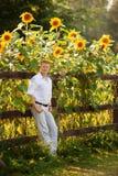 Человек готовит загородку около солнцецветов стоковое изображение