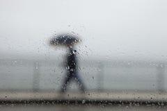 Человек гуляя под дождь стоковые изображения rf