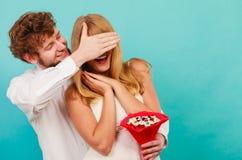 Человек давая пук конфеты женщины покрывая ее глаза Стоковые Изображения
