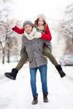 Человек давая piggyback женщины в установке зимы Стоковые Изображения RF