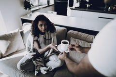 Человек дает чашку чаю подруги к обслуживанию от гриппа стоковое изображение rf