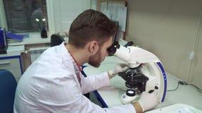 Человек двигает clipse этапа на микроскопе на лабораторию стоковые изображения