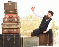 Человек, дворецкий с бородой и усик поставляют багаж, роскошную белую внутреннюю предпосылку Багаж и концепция путешествовать стоковая фотография rf