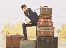 Человек, дворецкий с бородой и усик поставляют багаж, роскошную белую внутреннюю предпосылку Мачо элегантное на сотрясенной сторо стоковая фотография