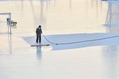 Человек делает лед на катке. Стоковые Фотографии RF