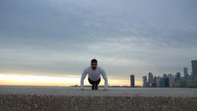Человек делает нажимает поднимает на ebankment Спортсмен тренируя outdoors Центр города с небоскребами на предпосылке взморье видеоматериал