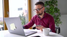Человек делает онлайн-платеж дома с кредитной карточкой и ноутбуком