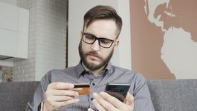 Человек делает оплату карточки банка онлайн на умном телефоне акции видеоматериалы