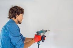 Человек делает отверстие в стене со сверлом стоковые фотографии rf