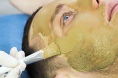 Человек делает процедуру очищая его сторону с маской глины в салоне красоты Стоковые Фото
