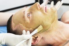 Человек делает процедуру очищая его сторону с маской глины в салоне красоты Стоковое Фото