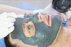 Человек делает процедуру очищая его сторону с маской глины в салоне красоты Стоковое Изображение