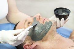 Человек делает процедуру очищая его сторону с маской глины в салоне красоты Стоковое фото RF