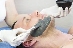 Человек делает процедуру очищая его сторону с маской глины в салоне красоты Стоковые Изображения