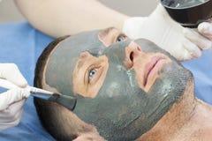 Человек делает процедуру очищая его сторону с маской глины в салоне красоты Стоковая Фотография RF