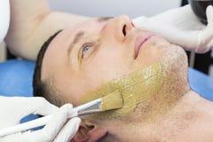 Человек делает процедуру очищая его сторону с маской глины в салоне красоты Стоковая Фотография