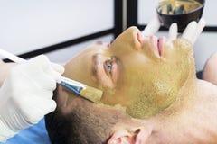 Человек делает процедуру очищая его сторону с маской глины в салоне красоты Стоковые Изображения RF