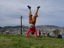 Человек делает Handstand на верхней части на холме перед зданиями стоковые изображения rf